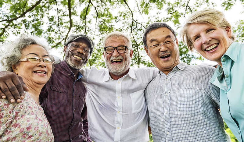 Seniors smiling, arms around each other, retirement planning