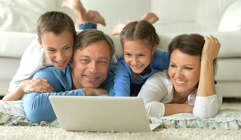 Family with young kids gathered around laptop, tax free savings