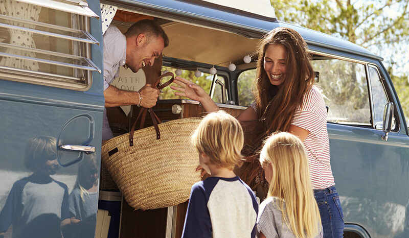 Family getting into camper van, travel insurance